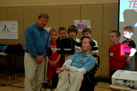 Students look on as Dick Hoyt explains how Rick's computer enables him to speak.