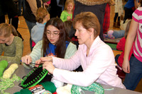 Troop Leader Linda Jannery helps with knitted hat making at MLK Day 2011.